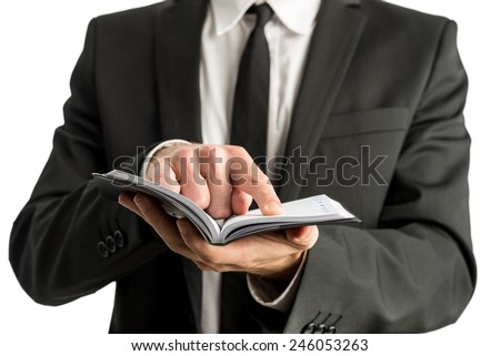Closeup of a businessman holding small notebook or planner as he pointing to one page, in a business planning concept. - stock photo