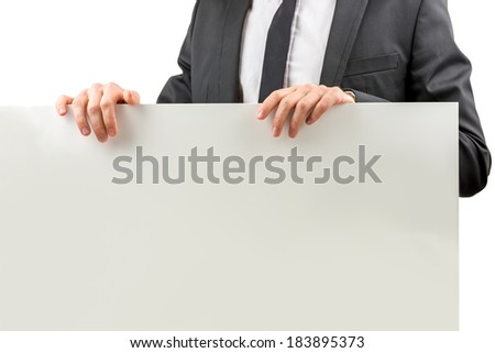 Closeup of a businessman in a suit holding a blank white rectangular sign with copyspace for your text or advertisement, torso view. - stock photo