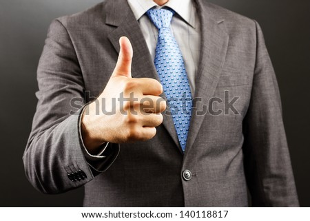 Closeup of a businessman showing thumb up  isolated on gray - stock photo
