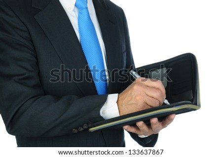 Closeup of a businessman taking notes in a small notebook. Hands and torso only, man is unrecognizable. Horizontal format over a white background. - stock photo