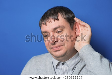 Closeup of a  businessman with hand behind ear listening closely  - stock photo