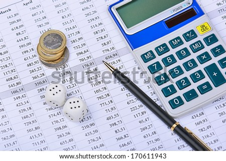 Closeup of a calculator, financial chart, coins, dice and pen. - stock photo