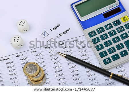 Closeup of a calculator, financial chart, coins, dice, pen and I agree-option. - stock photo