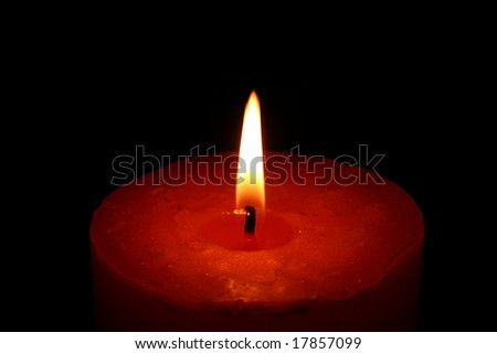 Closeup of a candle with black background - stock photo