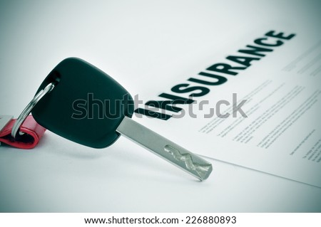 closeup of a car key and a insurance policy on a white surface - stock photo