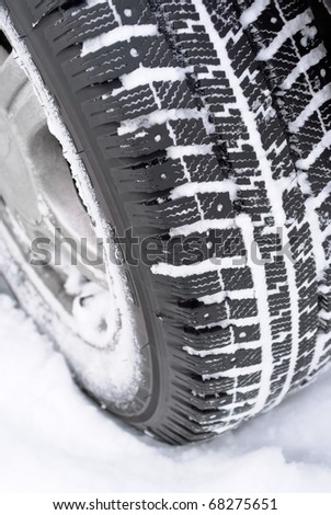 closeup of a car wheel with winter tire in snow - stock photo