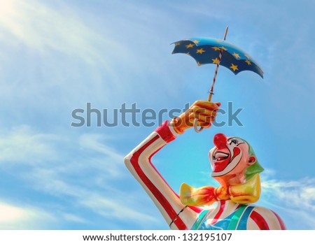 Closeup of a carnival clown statue with blue sky background and copy space - stock photo