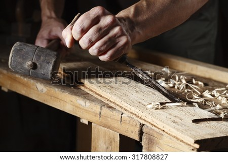 Closeup of a carpenter hands working with a chisel and hammer on wooden workbench - stock photo