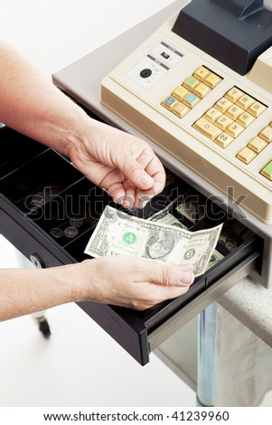 Closeup of a cashier's hands making change from a cash register. - stock photo