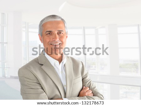 Closeup of a casual businessman in a modern office with his arms folded. Horizontal Format. - stock photo
