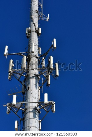 Closeup Of A Cellular Phone Tower Against Clear Blue Sky - stock photo