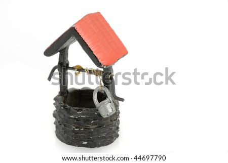 Closeup of a ceramic model of an old well.  Stone walls and red roof isolated on white background. - stock photo