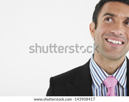 Closeup of a cheerful businessman looking up against white background - stock photo