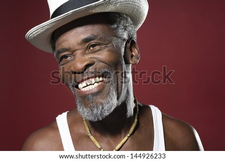 Closeup of a cheerful senior man in fedora against red background - stock photo