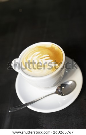 Closeup of a coffee cup on a dark table. - stock photo