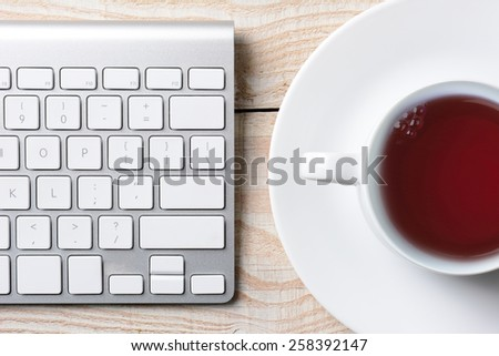 Closeup of a computer keyboard and cup of hot coffee on a white rustic table. High angle shot in horizontal format. - stock photo