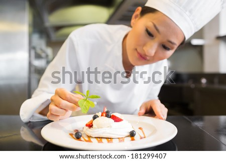 Closeup of a concentrated female chef garnishing food in the kitchen - stock photo