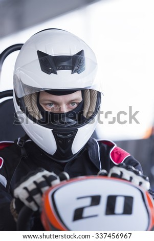 closeup of a concentrated karting driver sitting on his go-kart before starting a race in an outdoor go karting circuit - focus on the right eye - stock photo