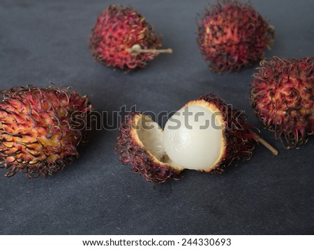 Closeup of a couple of rambutan fruits - one fruit is open  - stock photo