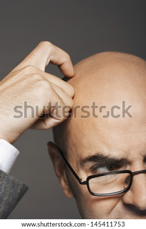 Closeup of a cropped businessman in glasses scratching bald head against gray background - stock photo