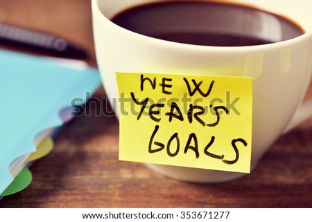 closeup of a cup of coffee with a yellow sticky note with the text new years goals written in it and a notebook and a pen on a rustic wooden table - stock photo