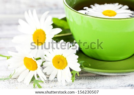 Closeup of a cup with herbal chamomile tea served in green ceramic cup and few wild flowers on white painted wooden surface - stock photo