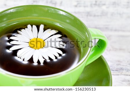 Closeup of a cup with herbal chamomile tea served in green ceramic cup on white painted wooden surface - stock photo
