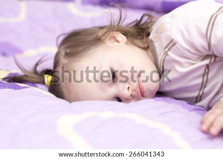 closeup of a cute baby girl laying in bed - stock photo