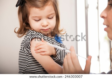Closeup of a cute little girl getting a flu shot at a doctor's office - stock photo