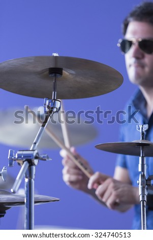 closeup of a cymbal with an unfocused drummer playing the drums and holding the drumsticks on background in a recording studio - focus on the cymbal - stock photo