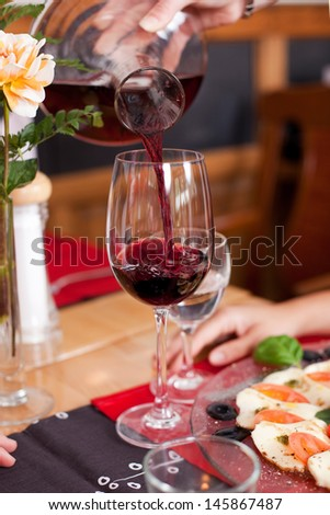 Closeup of a decanter of red wine being poured into an elegant long stemmed wineglass at a restaurant table - stock photo