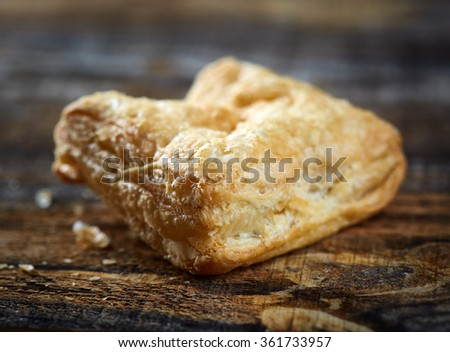 Closeup of a delicious pastry filled with cheese, on wooden board - stock photo