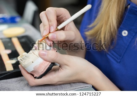 Closeup of a dental technician applying porcelain to a dentition mold in a lab - stock photo