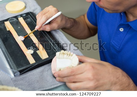 Closeup of a dental technician applying porcelain to a dentition mold with a brush in a lab - stock photo