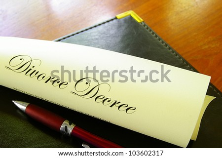 Closeup of a divorce decree, rolled up with pen - stock photo