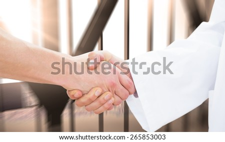 Closeup of a doctor and patient shaking hands against room with large window looking on city - stock photo
