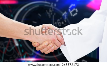 Closeup of a doctor and patient shaking hands against stocks and shares - stock photo