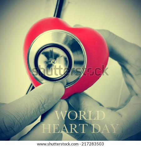 closeup of a doctor auscultating a red heart with a stethoscope and the text world heart day - stock photo