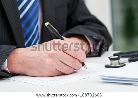 Closeup of a doctor's hands taking notes in his office - stock photo