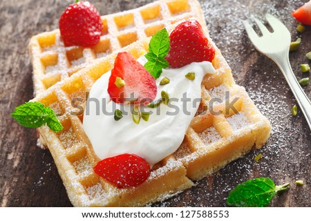 Closeup of a dollop of fresh whipped cream and sliced fresh strawberries topping a crisp golden waffle - stock photo