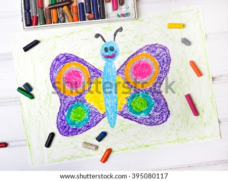 closeup of a drawing: happy butterfly with colorful wings - stock photo