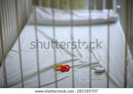 Closeup of a empty baby's crib with left toys - stock photo