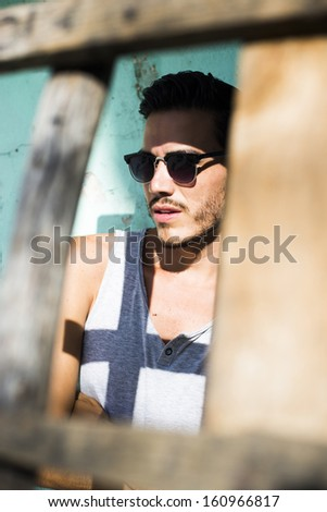 Closeup of a fashion model framed by a wooden ladder - stock photo