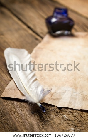 Closeup of a feather lying on vintage letter - stock photo