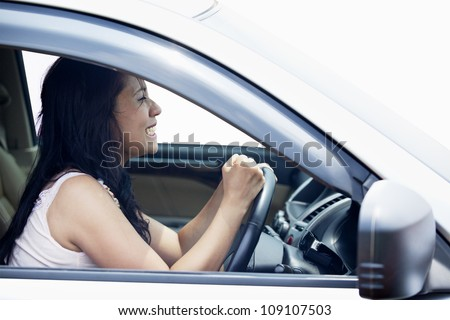 Closeup of a female driver angry punching the steering wheel - stock photo