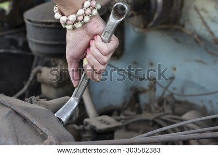 Closeup of a female hand holding wrench next to car radiator, concept of cars repair - stock photo