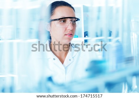 Closeup of a female researcher carrying out experiments in a laboratory - stock photo