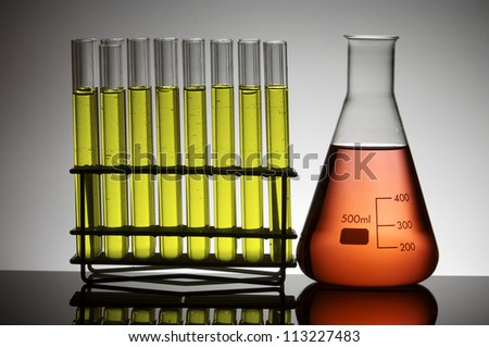 closeup of a flask and a group of test tubes - stock photo