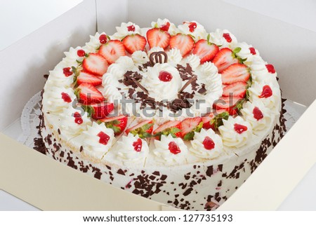 Closeup of a fresh strawberry cake with sliced strawberries and chocolate in a box - stock photo