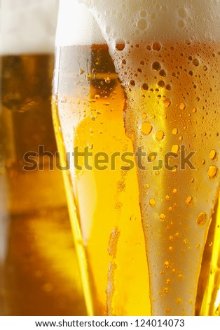 Closeup of a frothy cverflowing glass of golden ale or beer with liquid running down the outside of the glass, cropped view image - stock photo